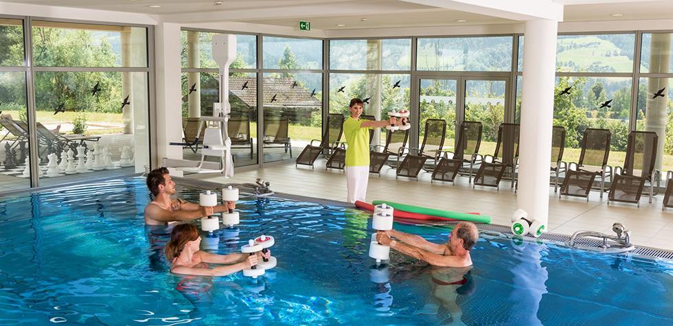 Hallenbad mit Wellnessliegen und Personen im Wasser