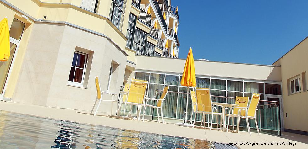 Gelbe Gartengarnitur mit Schirm vor einem Pool